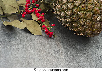 branch of holly and Ananas fruit on the grey background