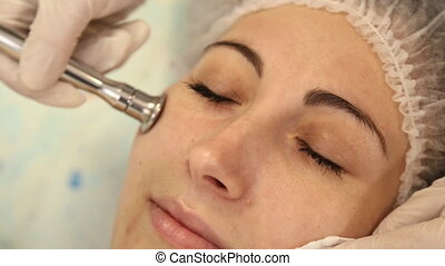 cosmetologist doing facial massage - Beautician doing a...
