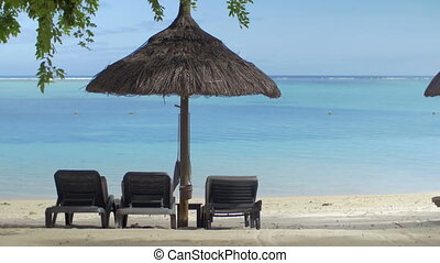 View of empty chaise-longue near native sun umbrella against blue water, Mauritius Island