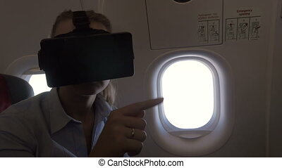 View of woman using VR-helmet for smartphone in airplane -...