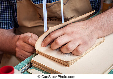 Bookbinding. Male worker binding pages. - Book binding...