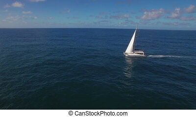 Aerial view of ocean, skyline and sailing yacht