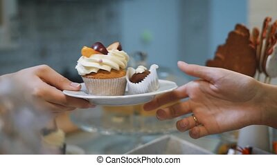 Pastry girl with colored nails sends a small white hand a...