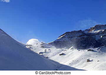 Off-piste slope during blizzard and sunlight blue sky....