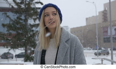 Beautiful girl posing in the street in winter