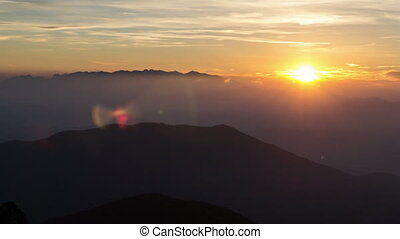 Colorful sunrise over mountain in foggy morning time lapse