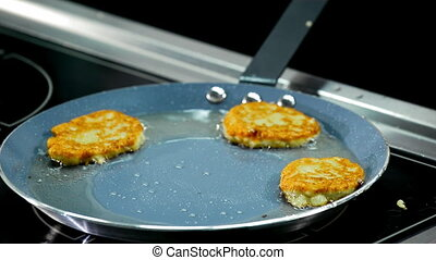 cooking potato pancakes in a frying pan.