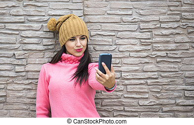 girl taking selfie with smartphone camera outdoors