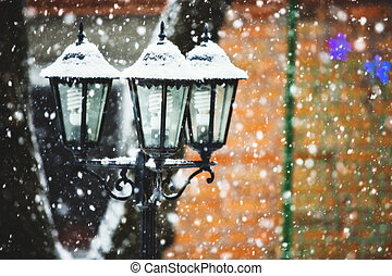 Street lamps in snowfall close up photo