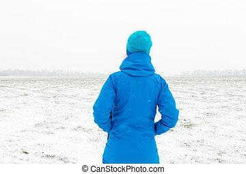 Woman in blue standing in a snowy field
