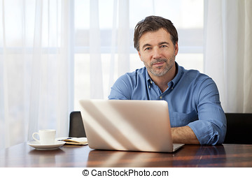 Handsome Man working At Home On His Laptop - Men, 50-59...