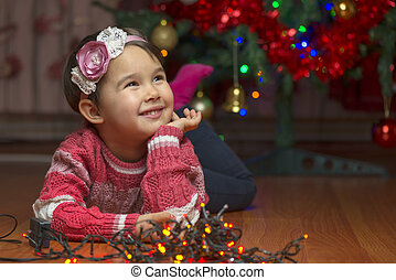 Portrait of cute little girl with Christmas tree on background