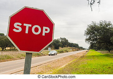 Red stop sign by the  road with cars in  Badajoz