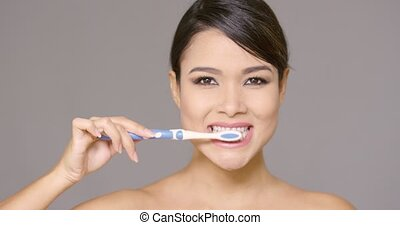 Sensual young woman cleaning her teeth with a toothbrush...
