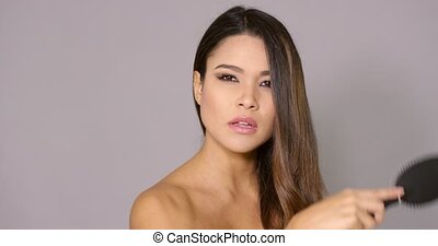 Attractive young woman brushing her long hair