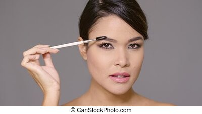 Pretty young woman contouring her eyebrows with a cosmetics...