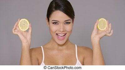 Smiling young woman holding lemons to her eyes - Smiling...