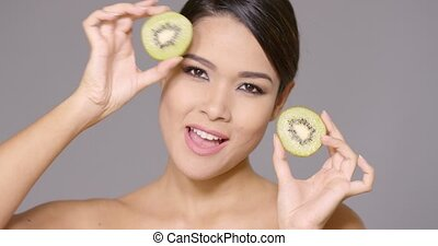 Vivacious young woman with a halved kiwifruit in each hand...