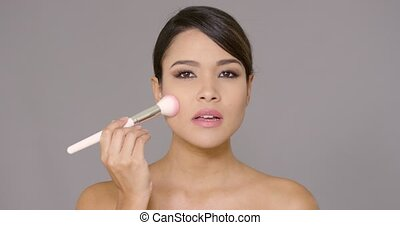 Sensual young woman applying blusher to her cheeks with a...