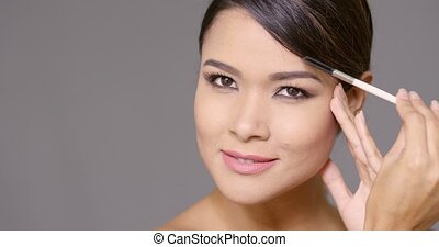 Young woman darkening her eyebrows applying makeup with a...