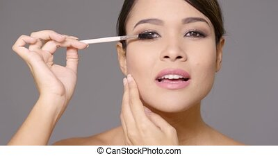 Young woman applying mascara to her eyelashes - Attractive...