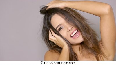 Carefree laughing young woman with long tousled brown hair...
