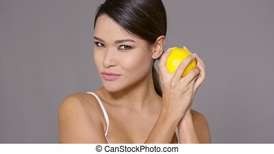 Cute young woman holding a halved fresh orange in each hand...
