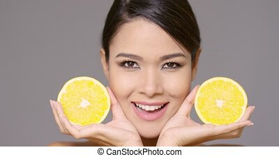 Pretty smiling woman holding lemon halves - Pretty smiling...