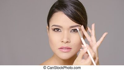Pretty young brunette woman applying makeup with a cosmetics...