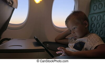Bored kid with pad in plane - Bored and tired child using...