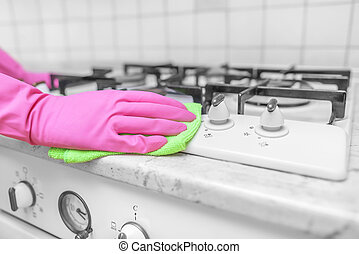 Hands in gloves are washed the gas stove.