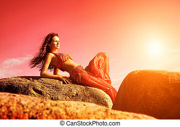 Woman in indian dress sitting on stones