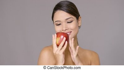 Young woman biting into a fresh red apple with her head...