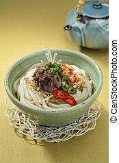 Korean Bulgogi Kimchi Udon in bowl with tea pot on the table