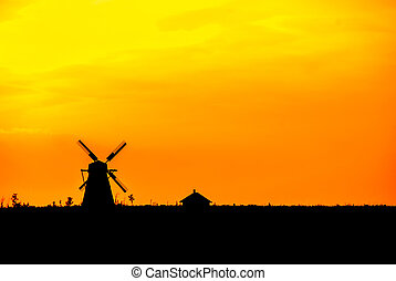 silhouette of an old historic windmill at sunset