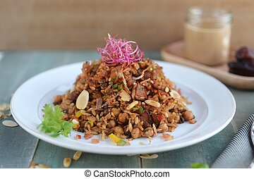 Fried rice in Indonesian style with seasoned pork and peanuts on white plate