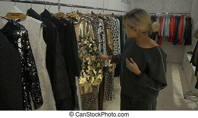 Young woman chooses a dress.