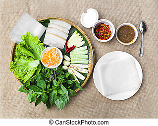 Vietnamese steamed thin rice pancake for pork rolls or banh uot Hue with lettuce, herbs and chili sauces