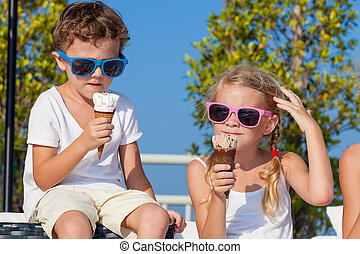 Three happy children eating ice cream near swimming pool at...