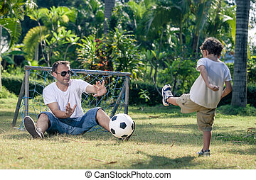 Father and son playing in the park at the day time. People...