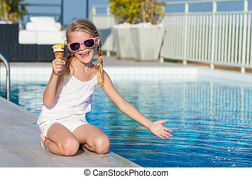 happy little girl with ice cream sitting near a swimming...