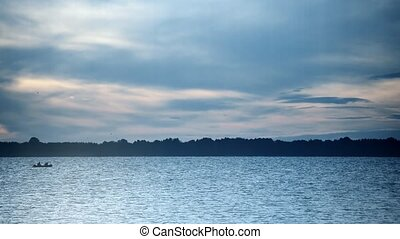 Silhouette of a boat at dusk on river during beautiful...