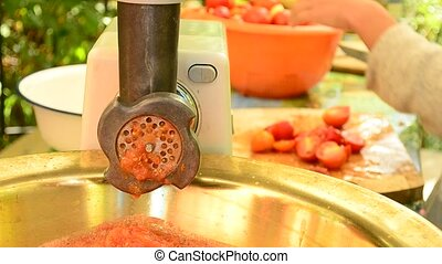 Making tomato sauce outdoors on mincing machine - Making...