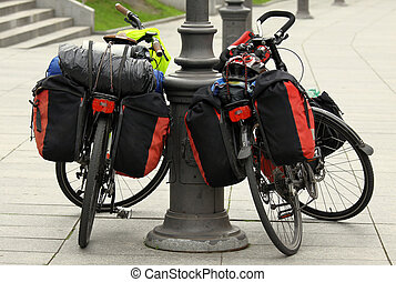 Two bicycles packet with travel bags resting on the city...