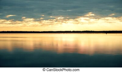 Time lapse of splendid clouds at dawn over water - Time...