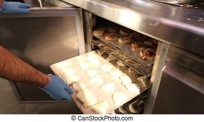 Pulling pastries tray from industrial fridge - Bakery worker...