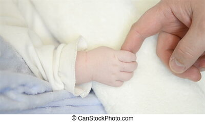 A new father holds his newborn infant baby's hand - Father...