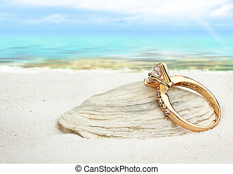 Jewellry ring with big diamond on sand beach with copy space, soft focus