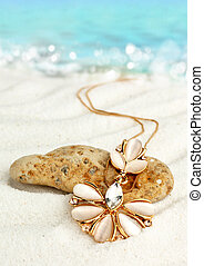 Golden jewellery pendant  on sand beach with sea background, soft focus