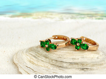 Jewellry earrings with emerald on sand beach with copy space, soft focus